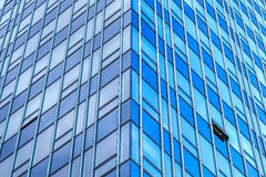 There must be an exception. Symmetrical image of glassy modern building, with one window open on northern side of the skyscraper Royalty Free Stock Photo