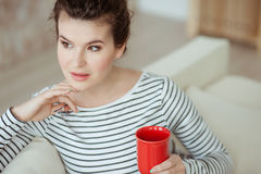There is no place like home. Cheerful young woman is enjoying hot drink. She is sitting on sofa and holding a cup. The lady is looking forward dreamingly royalty free stock photos