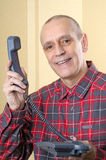 There is a Phone Call for You. A senior man giving the phone handset to somebody else - There is a call for you royalty free stock image