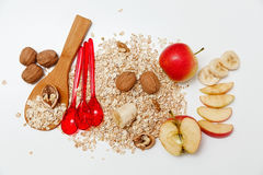 There are Pieces of Banana,Aple ,Walnuts and Rolled Oats,Wooden and Plastic Spoons,with Green Leaves,Healthy Fresh Organic Food on Stock Photo