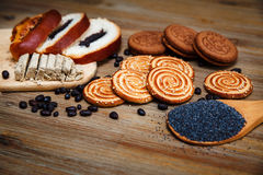 There are Pieces of  Roll with poppyseed,Cookies,Halavah,Chocolate Peas,Tasty Sweet Food on the Wooden Background Royalty Free Stock Photography