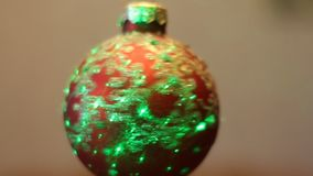 Ball with imitation of falling snow. There is a play of light reflected from surface of Christmas tree decoration stock footage