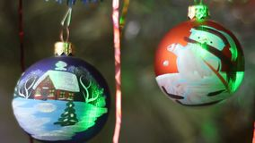 Christmas decorations. Two balls with imitation of falling snow. There is a play of light reflected from surface of Christmas tree decoration stock video footage