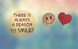 There is always a reason to smile with heart and smile emoji. There is always a reason to smile with wooden heart and smile emoji on bokeh light background stock image