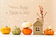 There is always a reason to smile message with pumpkins with a h. There is always a reason to smile message with collection of autumn pumpkins with a toy house stock image