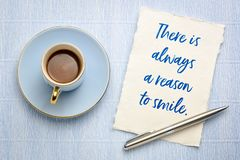 There is always a reason to smile. Handwriting on a small sheet of white Khadi rag paper with a cup of coffee royalty free stock image