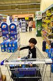 There`s a kid in a grocery cart stock photography