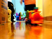 There's a life in motion. A toy train is moving forward while everything else but a boy in the background is still Stock Images