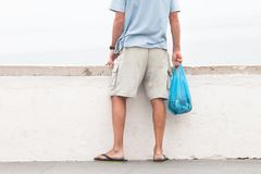 Old man with fish bag looking at the beach. There`s always more shopping to do. Old man with fish bag looking at the beach stock photography