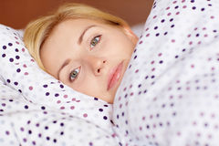 There's no getting up on Saturdays. A young woman lying awake in her bed Royalty Free Stock Photos