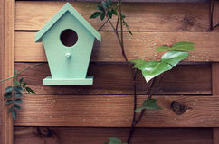 There`s no place like home. A turquoise bird house hanging from a fence Royalty Free Stock Image
