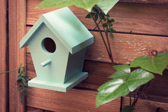 There`s no place like home. A turquoise bird house hanging from a fence Stock Image