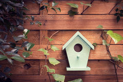 There`s no place like home. A turquoise bird house hanging from a fence royalty free stock photo