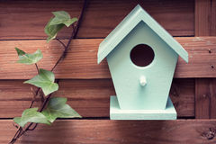 There`s no place like home. A turquoise bird house hanging from a fence Stock Photo