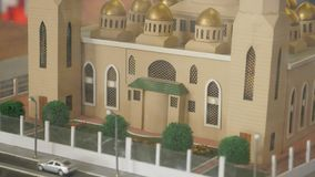 A close-up of the mosque layout. There is a Small Mock-Up of the Building on the Table in the Mosque. it Shows a Building With Golden Peaks, Growing Green Trees stock video