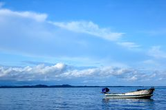Small white boat in the sea. There is a small white boat floating in the sea Stock Images