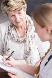 Is there something wrong with my results?. Shot of a concerned elderly women talking to her nurse Royalty Free Stock Photography