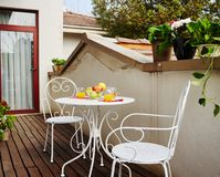 White wrought iron chairs and table on balcony stock photos
