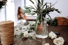 There is a vase with water and branches with green leaves and bobbin of twine on the table of florist royalty free stock image
