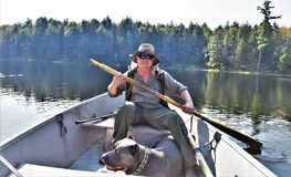 Massawepie lake adirondack boat man dog getaway. There is visitor of Massawepie lake with cane corso matiff on the boat , looking for rest in wildlife region of Stock Images