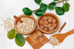 There are with Walnuts and Rolled Oats in the Wooden Plates with Sticks of Cinnamon,Wooden Support,Spoon,Green Leaves,Healthy Fres Royalty Free Stock Photos