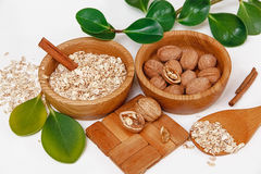 There are with Walnuts and Rolled Oats in the Wooden Plates with Sticks of Sinnamon,Wooden Support,Spoon,Green Leaves,Healthy Fres Royalty Free Stock Image