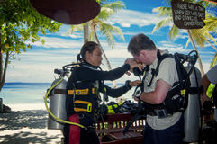 There was a time when sex was safe. A dive master help fixing a new student on breathing apparatus in SCUBA diving stock photography