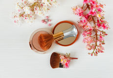 There White and Pink  Branches of Chestnut Tree,Bronze Powder with Mirror and Two Make Up Brushes are on White Table,Top View Stock Photo