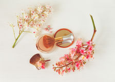 There White and Pink  Branches of Chestnut Tree,Bronze Powder with Mirrow and Make Up Brush are on White Table,Top View.Toned Stock Photos