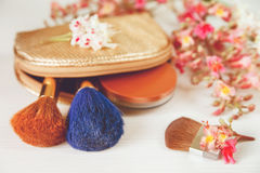 There White and Pink  Branches of Chestnut Tree,Bronze Powder;Two Make Up Brown and Blue Brushes in the Golden Cosmetic Bag are on Royalty Free Stock Photos