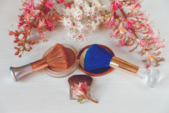 There White and Pink  Branches of Chestnut Tree,Bronze Powder,Two Make Up Brown and One Blue Brushes are on White Table,Toned Stock Photos