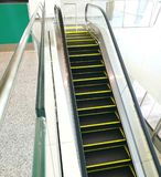 Escalator in an airport building. There are yellow lines outlining every steps for marking boundary of safety area; installed bollard on top to prevent and stop Royalty Free Stock Photos