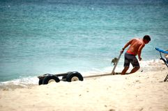 Young man dragging empty cart for jetski on beach stock images