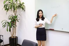 Asia Chinese office lady woman girl hand write success at whiteboard work smile wear business occupation suit workplace. There is a young pretty beautiful lady royalty free stock photography
