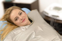 Thermal Blanket Treatment. Beautiful young woman getting thermal blanket treatment at beauty salon Stock Photo