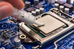 Thermal grease for computer. Computer main processor socket with CPU and thermal grease on the motherboard, view close-up stock photos