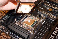 Thermal grease under copper heat sink on CPU. Small grain of thermal grease placed over the microprocessor for heat sink installation Stock Photos