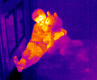 Thermal image of boy holding teddy bear stock image