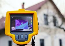 Thermal Imaging Detection. Recording Heat Loss of the Roof on the House with Infrared Thermal Camera in Hand Stock Images