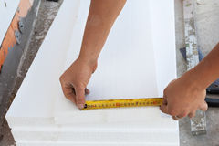 Thermal insulation house foundation walls with styrofoam boards. Worker use ruller to measure the  correct length of styrofoam. Royalty Free Stock Photography