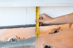 Thermal insulation house foundation walls with styrofoam boards. Worker use ruller to measure the  correct length of styrofoam. Stock Photography