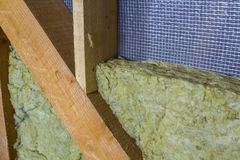 Thermal insulation mineral rock wool installation at the new bui. Lding attic wall Royalty Free Stock Photo
