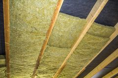 Thermal insulation mineral rock wool installation at the new bui. Lding attic ceiling Royalty Free Stock Photos