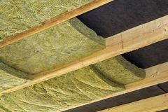 Thermal insulation mineral rock wool installation at the new bui. Lding attic ceiling Royalty Free Stock Photo