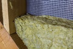 Thermal insulation mineral rock wool installation at the new bui. Lding attic wall Stock Image