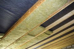 Thermal insulation mineral rock wool installation at the new bui. Lding attic ceiling Royalty Free Stock Images