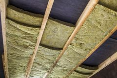 Thermal insulation mineral rock wool installation at the new bui. Lding attic ceiling Stock Image