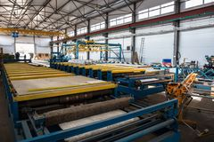 Thermal insulation sandwich panel production line for construction. Manufacturing storage with machine tools, roller conveyor. Industrial manufactory workshop stock photography