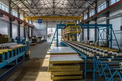 Thermal insulation sandwich panel production line. Machine tools, roller conveyor and gantry crane in workshop.  stock images