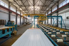 Thermal insulation sandwich panel production line. Machine tools, roller conveyor and overhead crane in workshop.  stock photography
